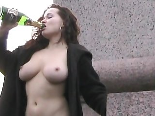 Curly redhead is drinking wine outdoors