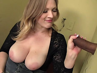 The arousing blonde gobbles cock at a gloryhole and the black guy cums for her.