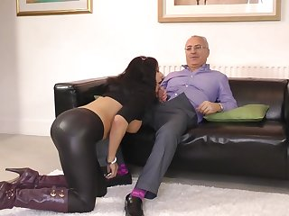 Awesome brunette girl with fake tits Carly G is showing her leggings on a sofa.