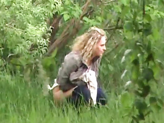 Slender blonde is pissing outdoors in the wild nature for a hot voyeur scene!