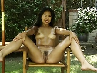 Exotic Asian model strikes some nude poses while outdoors