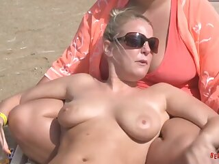 Girlfriends at the beach have big tits in bikinis