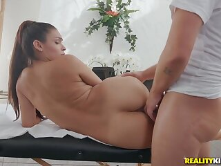 Shaved beauty on a massage table takes dick